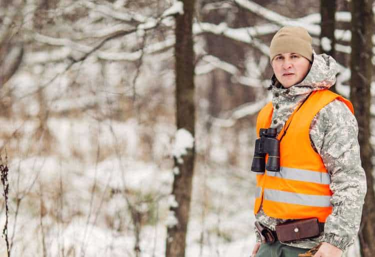 Male hunter in high vis vest, camouflage, standing in a snowy winter forest.